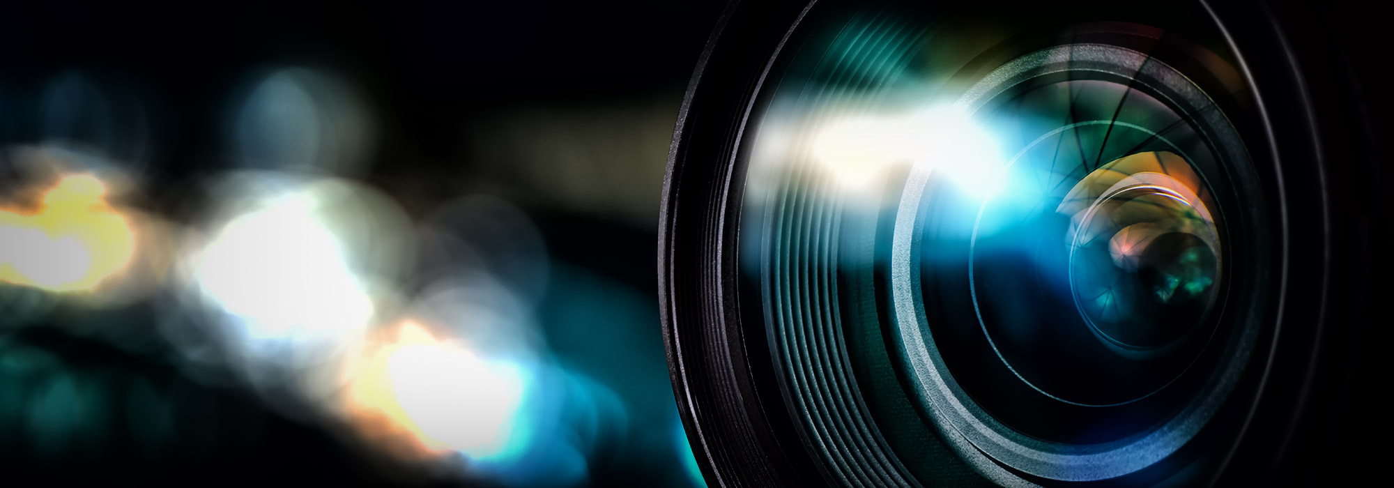 closeup view of a camera lense against a dark background with out of focus lights